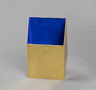 Thin-walled, open-work yellow gold cube in oblique configuration; stippled, matt outer surface; visible interior face with deep blue applied pigment.