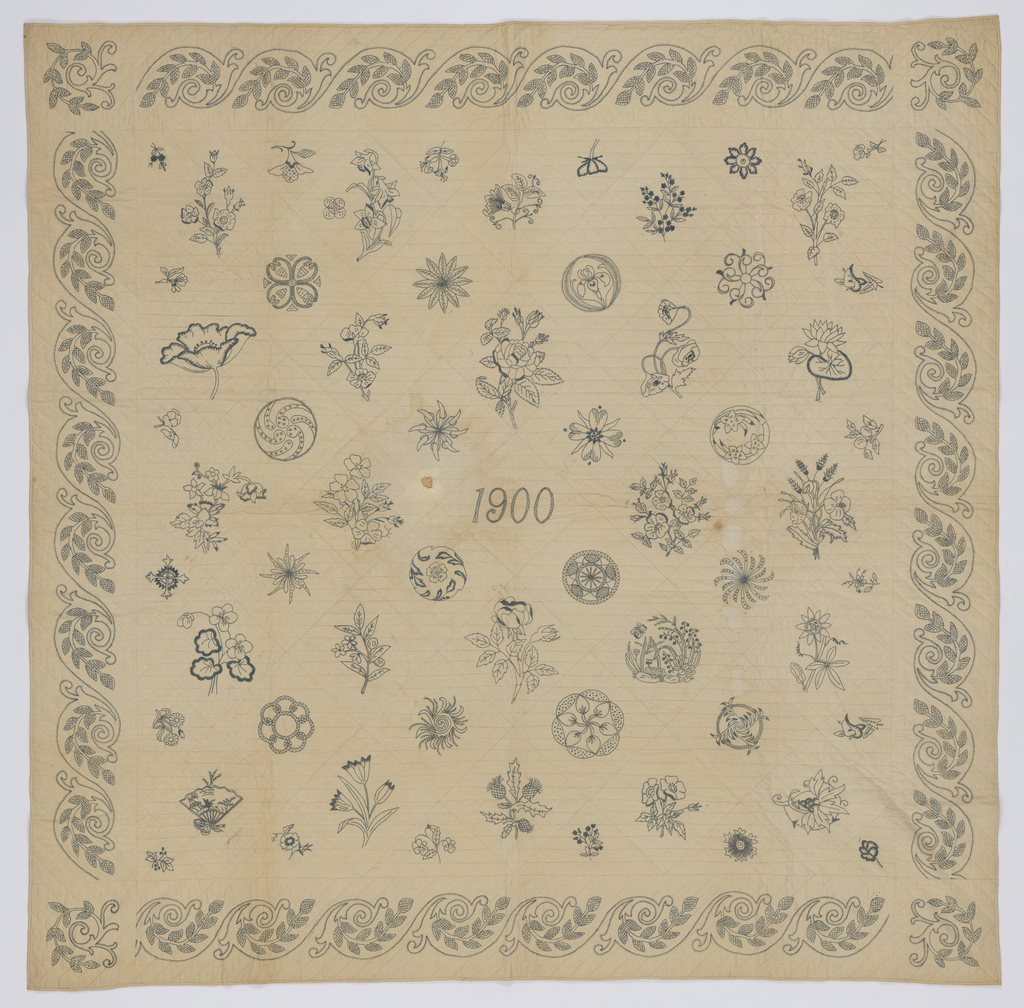 Patches embroidered with flowers and 'japonaise' patterns all in the same grey/blue thread on muslin foundation. The date 1900 is embroidered in the center and there is a repeating border around the edges. The outline the embroidery patterns is visible under the motifs. Backed with white cotton, quilted in straight lines.