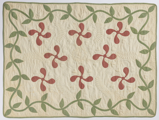 Crib quilt of white cotton with appliquéd design of red flowers and a green vine in printed cottons. Edged with the same green printed cotton. Quilted in the trapunto style, with heavily padded hearts and ferns.