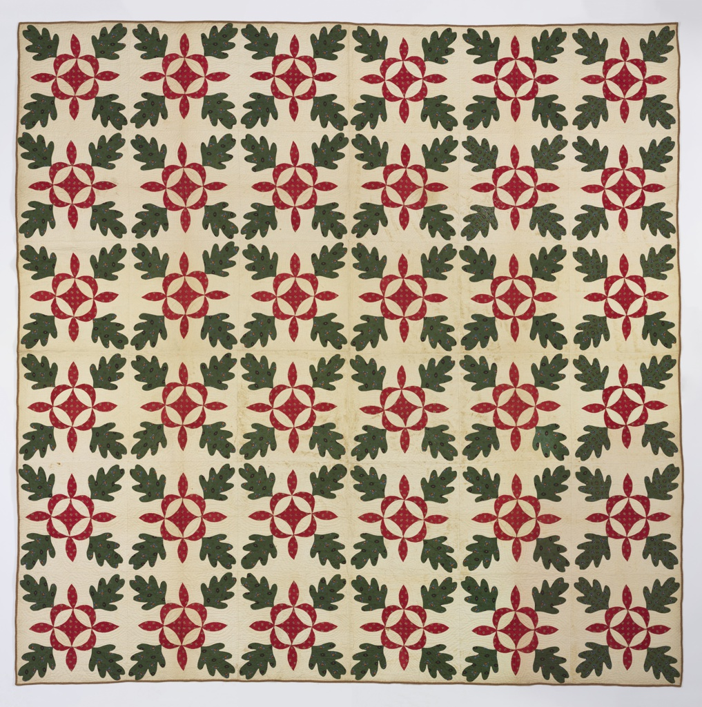Patchwork quilt in design of oak leaves in green print surrounding ornament of a diamond within a circle of red printed cotton. Backed with white cotton. Lines of quilting follow the pattern.