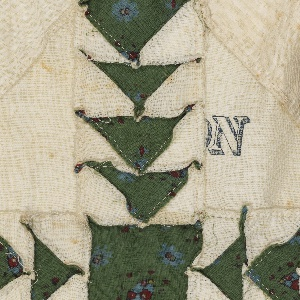 """Patchwork quilt top in """"Flying Geese"""" pattern in unbleached white cotton with roller-printed green cotton in a small-scale floral pattern. The white fabrics appear to be flour sacks or other wrapping fabrics, with fragments of printed text.   W (on front) and YOMING (on back) in gold FIN LONG CLO in blue and 36 YARDS on same square E  TH in blue (forming FINE LONG CLOTH) RAFT A in blue, type similar to FINE LONG CLOTH G (on front)"""