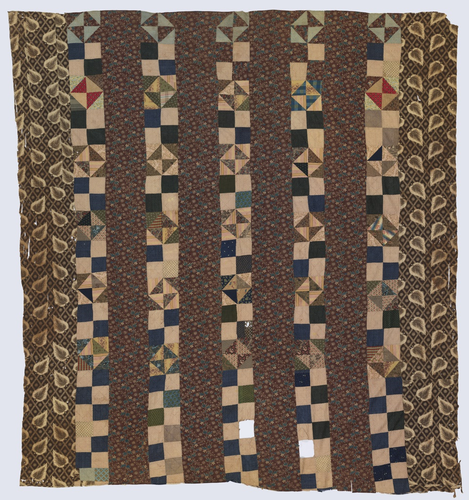 Patchwork quilt top made of six broad whole-cloth strips and five narrow patchwork strips. The patchwork strips are made up of small square and triangular pieces in tans, browns, and dark blue. The strips on the two outer edges have a very distinctive leaf pattern on a lattice ground in off-white on brown, while the whole-cloth strips in the center are a small-scale floral in blue and tan on a brown ground.