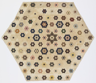 "Six-sided table cover made up of small hexagons in the  ""Garden Path"" pattern. Beautifully executed with close attention paid to the placement of printed motifs within the cut pieces. Lined with yellow and white seersucker (a later addition). Some paper patterns intact on the inside."