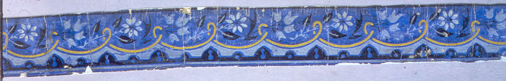 Printed in black, yellow and pale blue on dark blue ground, with scalloped scroll and floral sprays.