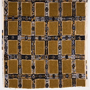 Grid of brown squares with intersecting borders of geometric patterning in dark blue, light blue, orange and white.