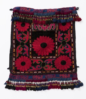 Pair of bags with a flap opening in the center. Black velveteen fronts, embroidered in a large-scale floral design in red with outlines in blue and green; inner and outer borders with a geometric design in yellow and off-white. Woven bands in indigo blue at top and bottom, embroidered with a scrolling design in two shades of red, ending in fringes in dark red, blue and black, wrapped with gold metallic yarns. Backing is red cotton with a discharge print in white of two paisleys, a star and cresent moon. Hanging loops at upper corners.