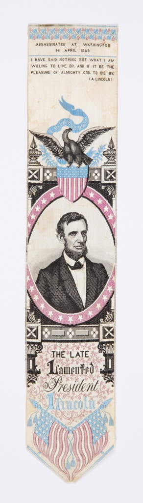 """Bookmark or stevengraph with a portrait medallion of Abraham Lincoln surmounted by an eagle perched on a shield flag that holds a banner in its beak that reads """"E Pluribus Unum."""" Inscription at top reads: """"Assassinated at Washington 14 April 1865,"""" and just below another inscription: """"I have said nothing but what I am willing to live by. And if it be the pleasure of Almighty God. To die by. (A Lincoln)"""