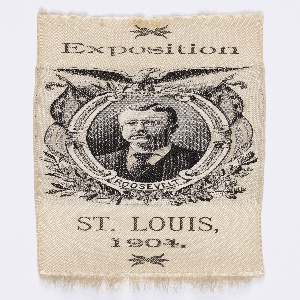 """Commemorative black and white bookmark of President Theodore Roosevelt made for the Louisiana Purchase Exposition, an international exposition celebrating the centennial of the Louisiana Purchase. Roosevelt is shown in a portrait medallion surmounted by an eagle. Inscription at top reads: """"Exposition."""" At bottom is another inscription: """"St. Louis 1904."""""""