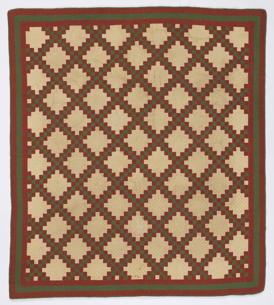 Patchwork quilt with a stepped squared diamond pattern in ivory, red and green. The ivory fabric forming the stepped diamond is plain. The red and green fabrics forming the lattice and borders are patterned by tiny flowers. The back is red with green edge.