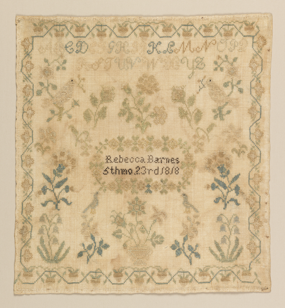 In the center, a floral wreath contains the inscription:  Rebecca Barnes 5th Mo 23 1818 Symmetrically arranged motifs of flowers and birds fill the field; there is one alphabet at the top. Surrounded on four sides by strawberry vine and floral borders.