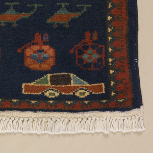 Prayer-rug sized carpet with dark blue ground, narrow border, and knotted fringe ends. The entire field is filled with profile views of tanks, helicopters, grenades, and automobiles in bright reds, oranges and greens.