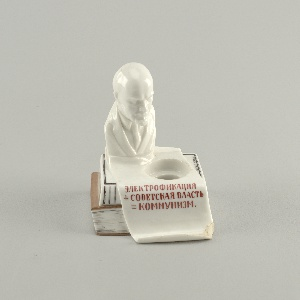 "In the form of two books, one sitting on top of the other, with a bust of Lenin resting on top; a scrolled paper-like form across the top and folding down the front side to form a pencil rest, inscribed (in Russian) ""Electrification + Soviet Power = Communism;"" circular hole for inkwell on top. Inscription on binding of lower book on back side (in Russian): ""N. Lenin / (V. Ulyanov) / Volume X / Collected / Works."" Inscription on top side of upper book (in Russian): ""Publishing House of the Sea Ministry""[?"