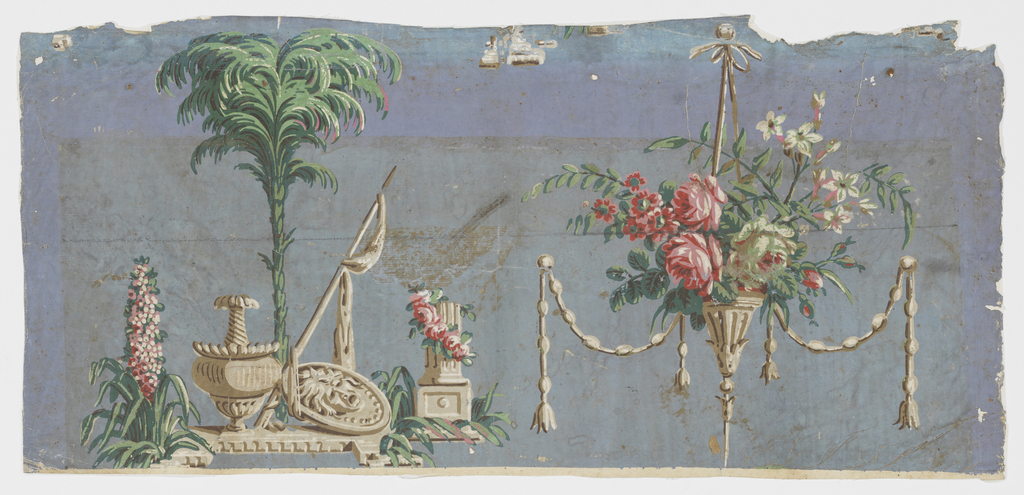 Whole width of paper, but incomplete repeat. On blue, faded ground a vase, a shield, a drapery-hung spear and a flower-decorated column fragment grouped under a palm tree. To the right, conical flower holder with bouquet and tasseled ropes.