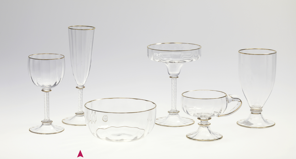 Mouth-blown crystal champagne flute, with a twisted stem and a structured cup with gold rims.