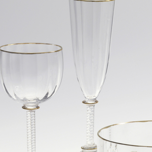 Mouth-blown crystal champagne cup, with a twisted stem and a structured cup with gold rims.