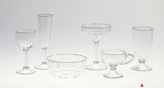 Mouth-blown crystal water glass, with a twisted stem and a structured cup with gold rims.