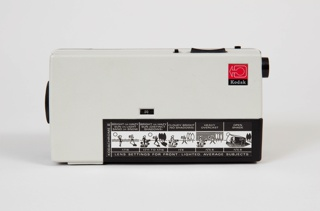 Rectangular bi-colored, molded plastic body; circular lens at front, slightly left of center; a row of five drawings appear on the battery slot cover on proper left side; Kodak logo in upper lefthand corner of proper right side; switch at top back left.