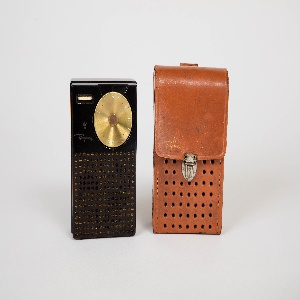 Rectangular molded plastic body with perforations for speaker covering 2/3 of front face; brass circular dial at top right  for adjusting frequency and white plastic dial for power and volume and tuning control at top left; Regency in script with crown symol above at bottom left