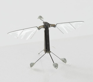 Bee-sized robot consisting of a black vertical post with two transparent wings projecting from upper left and right sides; supported by three slim legs in a tripod configuration.