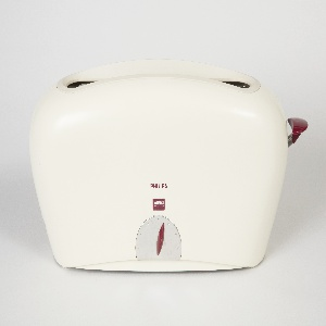 Beige, tapering rectangular form with rounded edges, reminiscent of a pillow; top with wide slit and basket to accept bread slice; front face with small burgundy-colored oval control knob and calibrations at center, bottom; Burgundy-colored tab on right to lower toast basket.