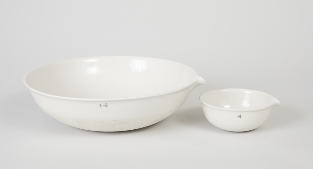 Small circular bowl with spout at one side, white pocelain body glazed white.