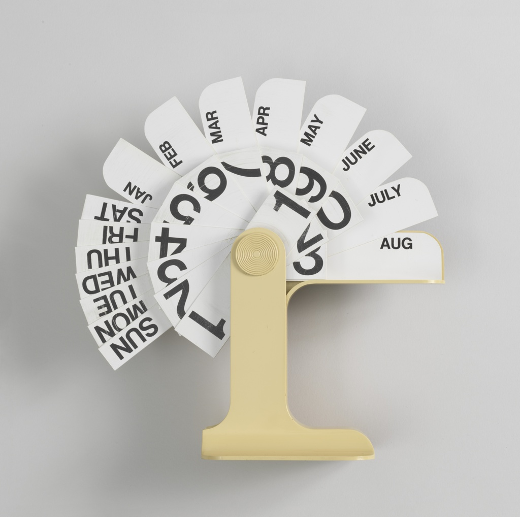 Plastic cream colored base of roughly inverted L shape, holding white plastic tabs with date numbers, months and days of the week; tabs pivot from bar on left.