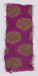 Firm cerise twill ground brocaded in gold with fairly close-set oval medallions formed of stylized flowering tree.