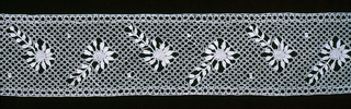 Narrow band of lace worked in a provincial style with a pattern of small blossoms.