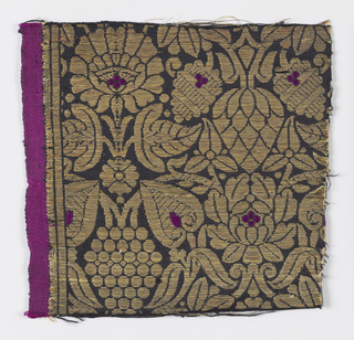 Close-set medium-scale repeat of symmetrical stylized print and flower motifs in gold with bright cerise details on black ground. Wide satin selvage with cerise silk warps set off by two stripes formed by metal floats, one with cotton cord under floats.