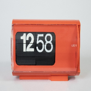 Cylindrical, table clock in red molded plastic with a clear front to reveal two wheels of plastic flaps with large white numbers on a black background.