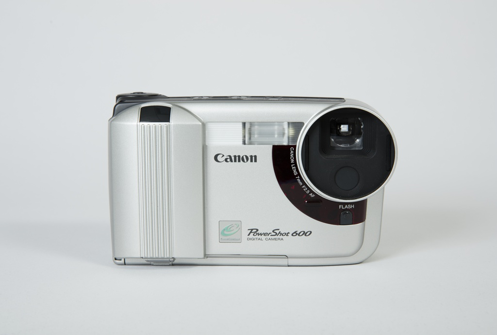 Digital camera and docking station. Camera with molded plastic, bulbous rectangular body with rounded edges; circular 7.5mm lens at front right. Black plastic panel with control buttons along top and back. Canon logo and camera model number at front bottom.