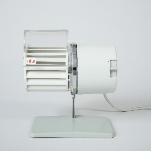 Horizontally-oriented, cylindrical white plastic desk fan; left-hand section composed of long, closely spaced horizontal fan blades with clear plastic hood with Braun logo; right hand section comprising motor housing with power/speed switch at right edge; rectangular enameled steel base with chrome-plated steel stem.