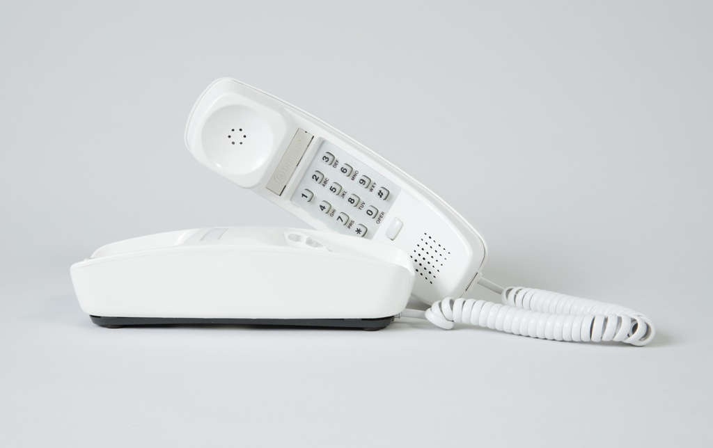 White telephone with curved handset with flat touch tone dial and base with modular plug