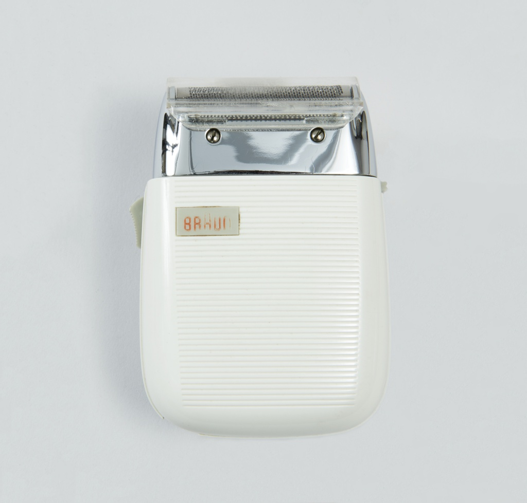 White plastic housing, lined surface, rounded edges, metal top with razor blades. Clear plastic tip to protect razor blade. Grey plastic switch at left.