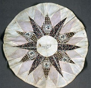 """Patchwork medallion with a star pattern in unbleached cotton and three roller-printed cottons in browns, tans and pinks. Handwritten in dark brown ink in the center circle; """"Olivia C. Whitridge, New Bedford, 1853"""""""