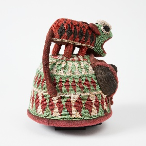 Beaded hat depicting a leopard on top of a face with exaggerated features. Scarification depicted as three vertical lines under the eyes.