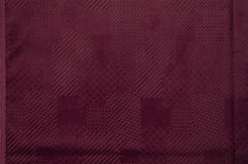 Maroon corduroy with an irregular grid of twill patterns.