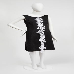 Black cotton taffeta with a single vertical column of white embroidery down the center.  The 37 three-dimensional embroidered motifs include butterflies, birds, flowers, and the word PEACE.