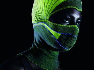 Balaclava knitted in black and neon green, with reflective stripes and knitted in electroconductive yarns to heat the mesh in the mouth area.