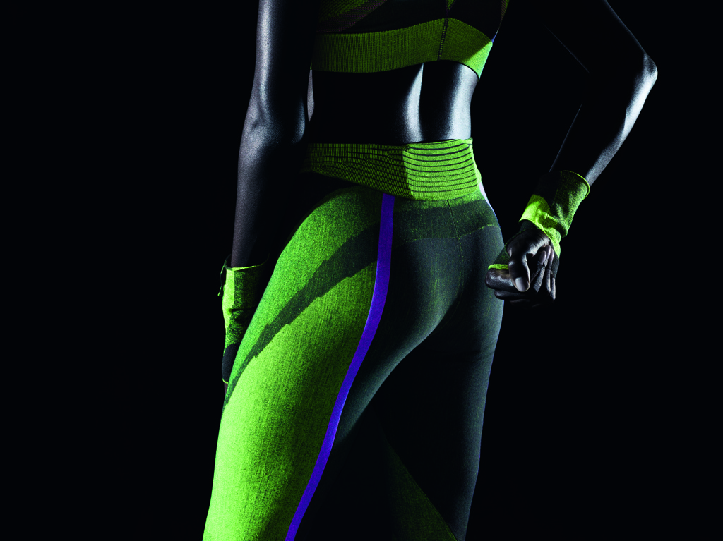 Pair of running tights, knitted in black and neon green, with reflective stripes and 3D shaping. With knitted-in cell phone pocket at back waistband.