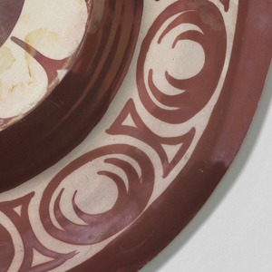 A dark red plate decorated with a border of cream-colored nude males around the inner plate and outer rim.