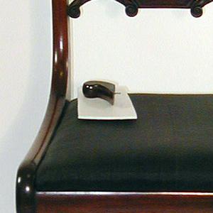 Back legs flat sided, front legs flat excepting rounded front face; legs curve outward toward bottom, and back legs incline toward eachother at bottom.  Corner posts of back in a double curve terminating at top in on elemenatary volute form.  Flat top rail bowed toward back, slightly arched, with a rectangular panel of inset veneer surrounded by beading.  Splat horizontal, composed of small oblong faced with veneer, flanked oneither side by horizontal coupled C-scrolls deeply carved with foliage, terminating in volutes.  Seat flares  from back to front with straight edges.