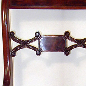 Back legs flat-sided, front legs flat excepting rounded front face; legs curve outward towar bottom, and back legs incline toward each other at bottom.  Corner posts of back terminate in a double curve with elementary volute form.  Flat top rail bowed toward back, slightly arched, with a rectangular panel of inset veneer surrounded by beading.   Splat horizontal, composed of small oblong faced with veneer, flanked on either side by horizontal coupled C-scrolls deeply carved with foliage, terminating in volutes.  Seat flares from back to front, with straight edges.