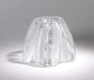 A shaped open domed form with ridges of glass coil around it.