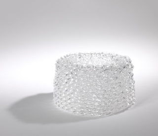 Loops of continuous glass create a filigree-like pattern in a cylindrical form.