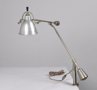 Brass-colored lamp in which the lampshade is held by a metal rod ending in a wishbone shape. There is one handle at the end of the metal rod that holds the lampshade and one handle for the metal rod that is attached to the desk support.
