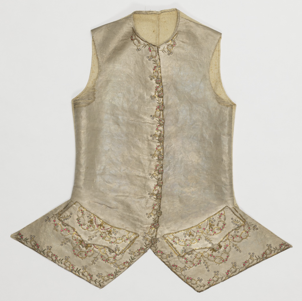 Gentleman's waistcoat in off-white silk with metallic, embroidered lightly on the front and lower edges and pocket area with gold thread, colored metallic sequins and coils of wire.