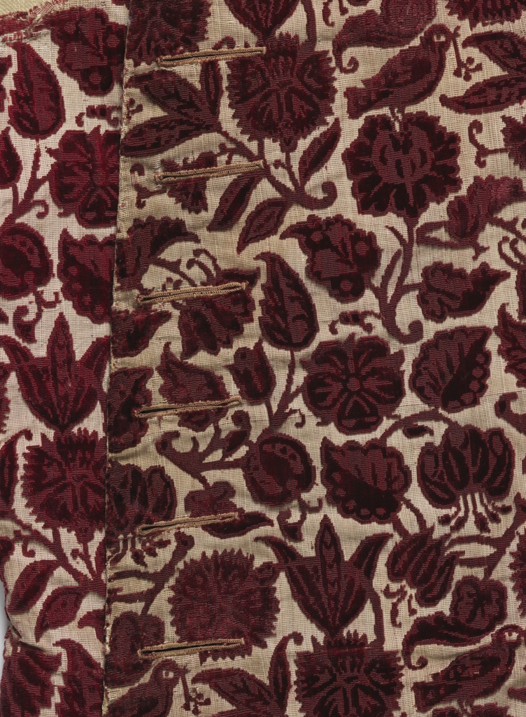 Waistcoat made from velvet in an allover design of flowers and birds in dark red on a tan ground.