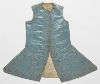 Gentleman's full-skirted waistcoat of blue satin with monochrome embroidery of floral forms worked heavily along the front and lower edges and pocket area. White silk moire lining in skirt.