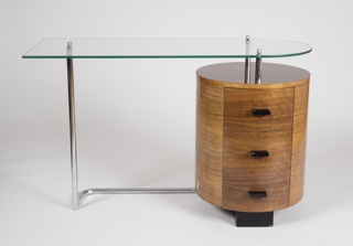 Assymetrical form composed of planar, transparent glass top, squared at left end, curved at right, mounted on tubular steel base with cylindrical shaped wooden drawer unit on right side; three drawers with dark wooden pulls.